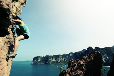 rock wall: free solo woman rock climber climbing at seaside mountain rock wall Stock Photo