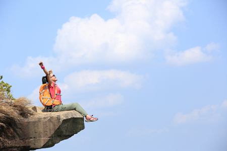 cheering young woman hiker enjoy the view at mountain peak cliff Imagens - 55371178