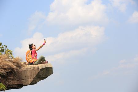 jonge vrouw wandelaar die foto met slimme telefoon op bergtop cliff