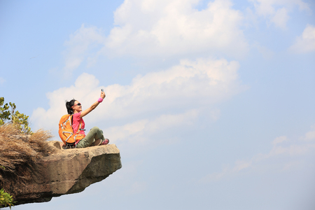 young woman hiker taking photo with smart phone at mountain peak cliff