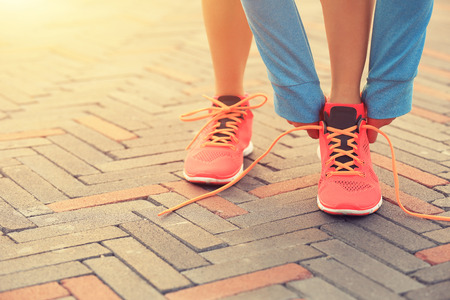 red tie: young woman runner tying shoelaces on city road