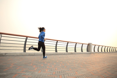 active people: young fitness woman runner runnin on seaside bridge