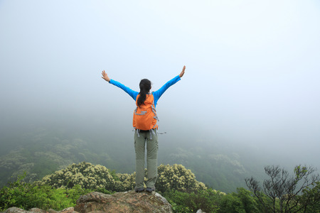 open arms: cheering young asian woman open arms on spring mountain peak Stock Photo