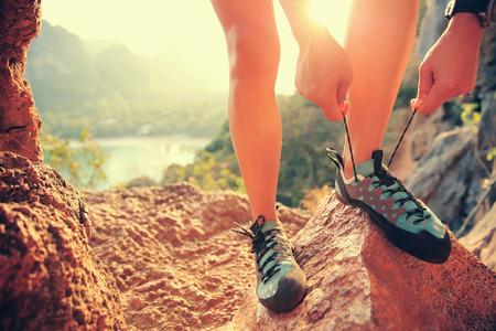 shoelace: rock climber tying shoelace outdoor