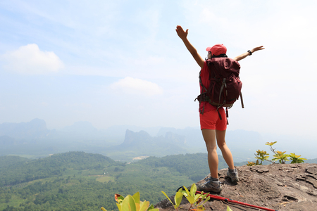 open arms: cheering woman hiker open arms at mountain peak Stock Photo