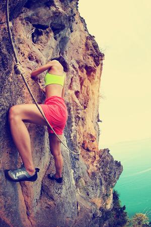 lead rope: young woman rock climber climbing at seaside mountain rock