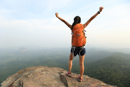 red mountain open space: cheering successful woman hiker open arms at mountain peak