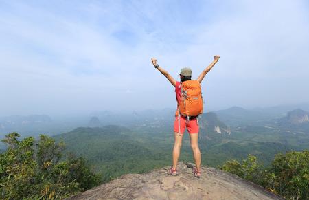 ser humano: animando mujer joven caminante disfrutar de la vista en el pico acantilado de la montaña Foto de archivo