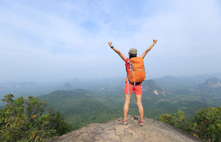 red mountain open space: cheering young  woman hiker  enjoy the view on mountain peak cliff