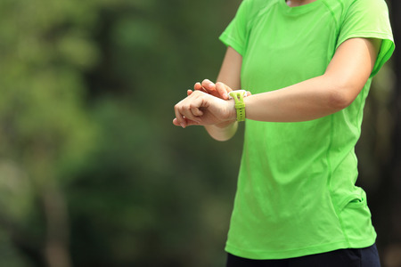 pulse trace: young woman jogger ready to run set and looking at sports smart watch, checking performance or heart rate pulse trace.