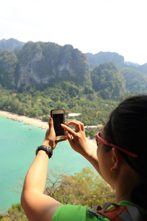 taking photo: hiker hands taking photo with smartphone at seaside
