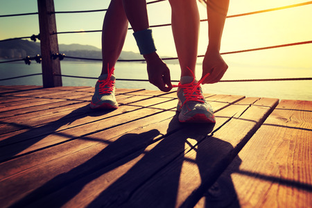 shoelace: young fitness woman runner tying shoelace at seaside boardwalk