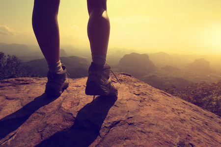 young woman hiker legs on mountain peak rock Reklamní fotografie