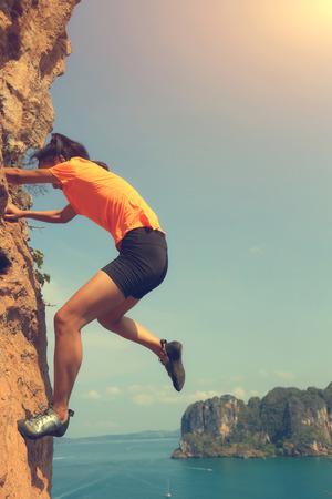 free climber: free solo woman rock climber climbing at seaside mountain rock wall Stock Photo