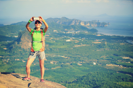 taking photo: young woman hiker use smartphone taking photo on seaside mountain top