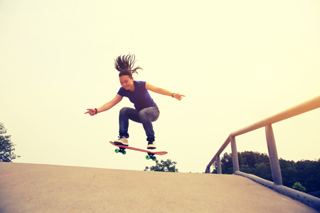 ramp: skateboarding woman practice ollie at skatepark ramp