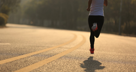 legging: young fitness woman runner running on road Stock Photo