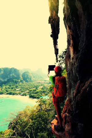 taking photo: woman hiker taking photo with digital tablet at seaside mountain cliff