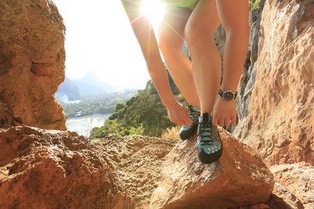 shoelace: young woman rock climber tying shoelace outdoor