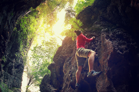 young woman rock climber climbing at mountain cliff Stock Photo