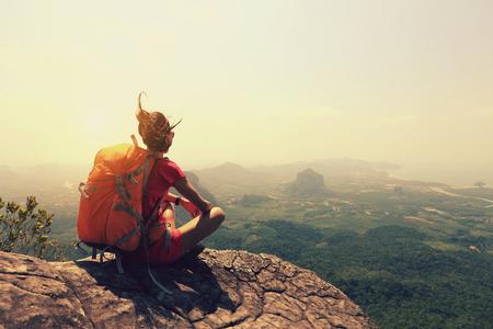 young woman backpacker hiking on seaside mountain peak