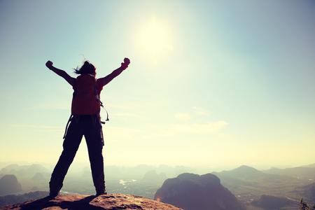 juichen vrouw wandelaar open armen bij zonsopgang bergtop