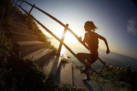 cross country: fitness woman trail runner running on seaside mountain stairs, training for cross country running.