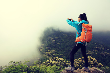 young woman hiker use smartphone taking photo on mountain top