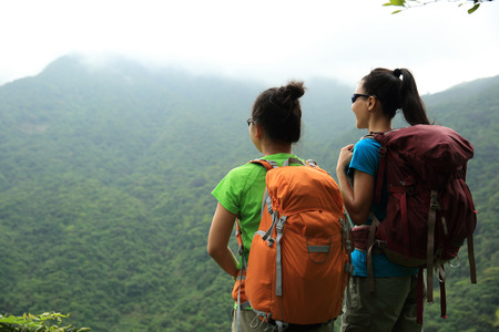 two successful hikers enjoy the view on mountain peak
