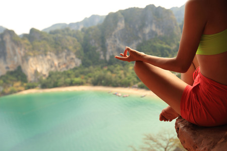 sea cliff: young healthy woman practice yoga on mountain peak cliff