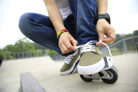 shoelace: freeline skateboarder tying shoelace at skatepark ramp Stock Photo