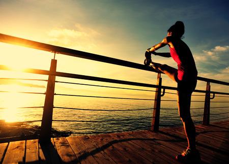 warm up: healthy lifestyle sports woman runner warm up on wooden boardwalk sunrise seaside Stock Photo