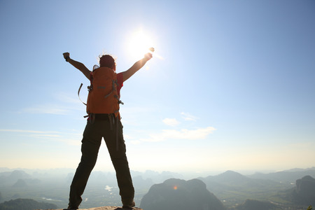 red mountain open space: cheering woman hiker at sunrise mountain peak Stock Photo