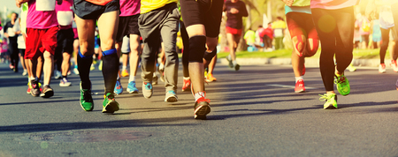 crowded space: Unidentified marathon athletes legs running on city road