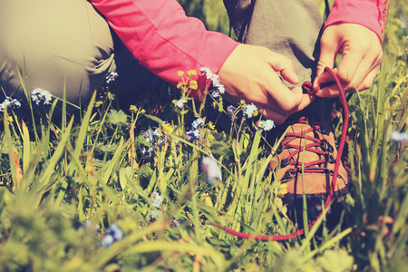 shoelace: woman hiker tying shoelace on grassland grass