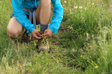 shoelace: young woman hiker tying shoelace on trail in grassland