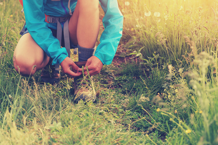 shoelace: young woman hiker tying shoelace on grass trail Stock Photo