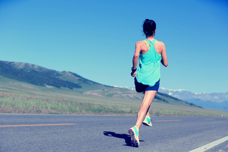 outdoor training: healthy lifestyle young fitness woman runner running on road