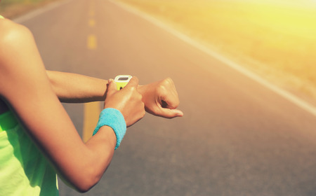 pulse trace: young woman runner ready to run set and looking at sports smart watch, checking performance or heart rate pulse trace. sport and fitness outdoors .