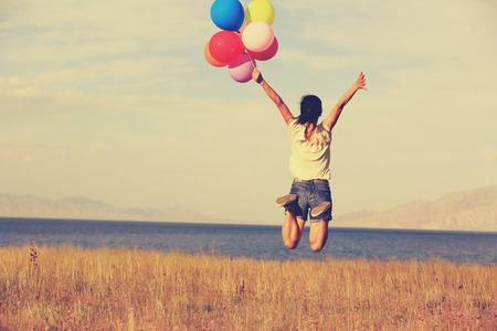 red mountain open space: cheering young asian woman jumping on grassland with colored balloons