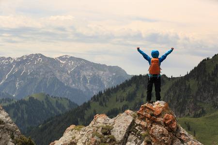 juichen succesvolle vrouw backpacker open armen op bergtop