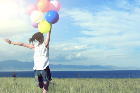 red mountain open space: cheering young asian woman running on sunset grassland with colored balloons