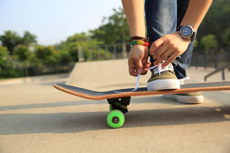shoelace: skateboarder tying shoelace at skatepark ramp