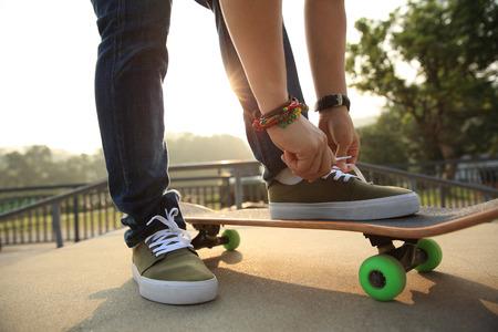 shoelace: skateboarder tying shoelace on skatepark