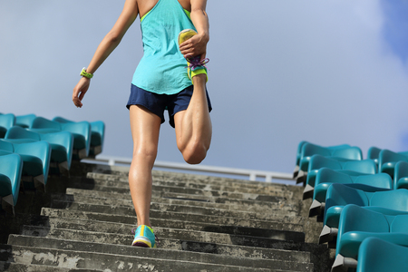 warm up: young fitness woman runner warm up on stairs