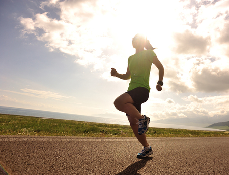cross legs: healthy lifestyle young fitness woman runner running on sunrise road Stock Photo