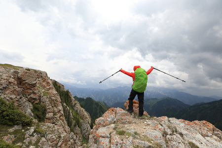 open arms: cheering successful woman backpacker open arms on mountain peak