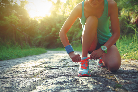 young woman trail runner tying shoelaces in forest Stock Photo