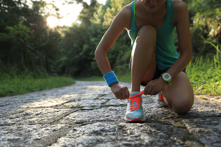 cross ties: young woman trail runner tying shoelaces in forest Stock Photo