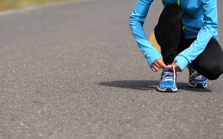 shoelace: young  woman runner tying shoelace on road